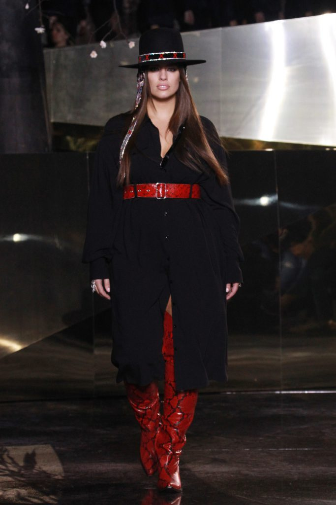 Walking in a non plus size model show fashion week for H&M in a black shirt dress and daring red thigh-high boots.