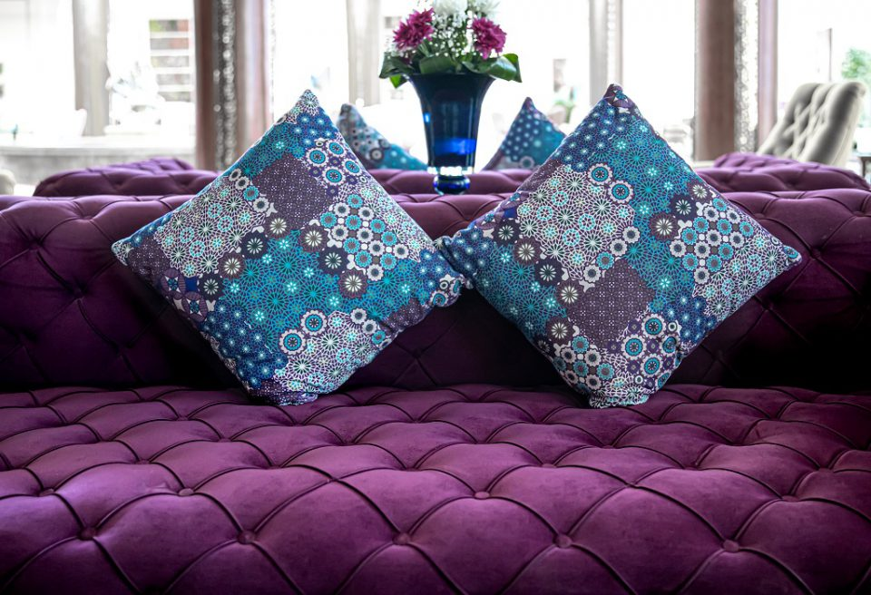 Purple velvet fabric modern sofa with sunken buttons and colorful decorative pillows.
